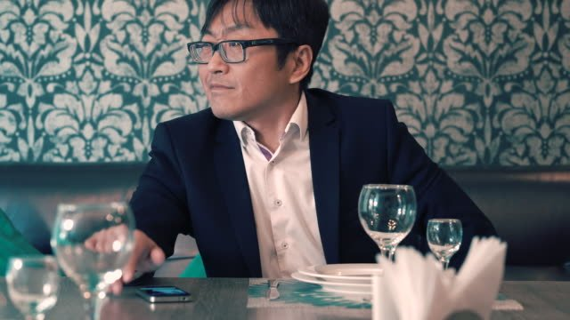 Asian-man-in-suit-businessman-waiting-in-the-cafe-their-food-Long-waits-for-ordering-Nervous