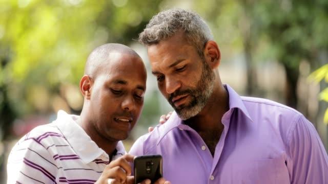 Glücklich-Lgbt-Gay-paar-betrachten-von-Bildern-auf-dem-Handy