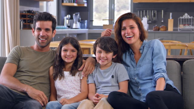 Portrait-Of-Smiling-Family-Sitting-On-Sofa-In-Lounge-Together