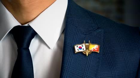 Businessman-Walking-Towards-Camera-With-Friend-Country-Flags-Pin-South-Korea---Bhutan