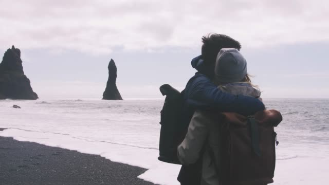 Junges-paar-umarmt-und-Enjoing-Blick-auf-schwarzen-Sandstrand-in-Island-Slow-motion