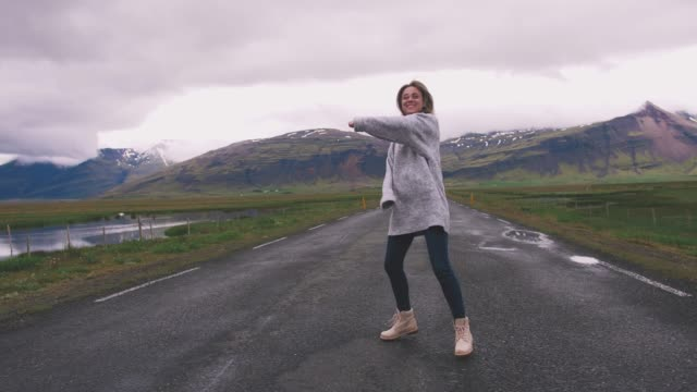 Happy-young-woman-dancing-on-asphalt-road-in-Iceland-and-having-some-fun-slow-motion