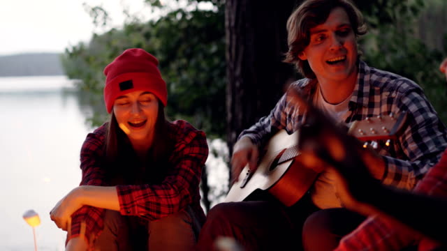 Multiracial-group-of-tourists-is-having-fun-in-forest-playing-the-guitar-and-singing-songs-around-campfire-in-wood-near-lake-People-are-wearing-casual-clothing-