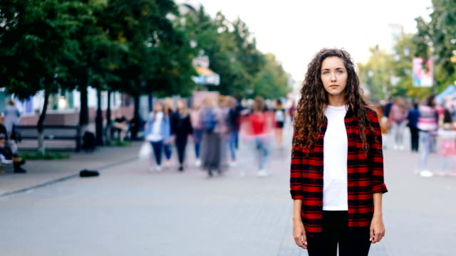 Time-lapse-portrait-of-confedent-young-woman-standing-alone-in-the-street-on-summer-day-and-looking-at-camera-while-people-are-whizzing-around-in-hurry-