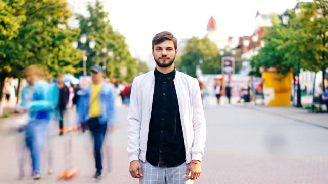 Time-lapse-portrait-of-serious-young-man-looking-at-camera-standing-in-center-of-busy-pedestrian-street-in-summer-wearing-stylish-clothing-while-people-are-passing-by-