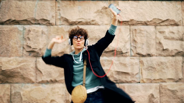 Mujer-joven-feliz-melómano-es-cantando-y-bailando-escuchando-música-en-auriculares-y-sostiene-el-teléfono-inteligente-al-aire-libre-en-la-calle-Concepto-de-canciones-y-de-la-juventud-