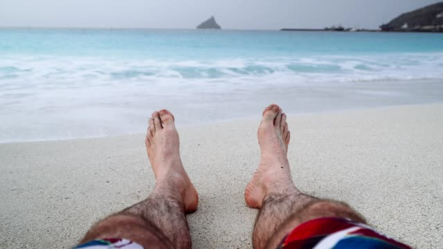 Mans-feet-on-sandy-beach-Vacation-and-relaxation-concept-beach-holidays-background-4k-video