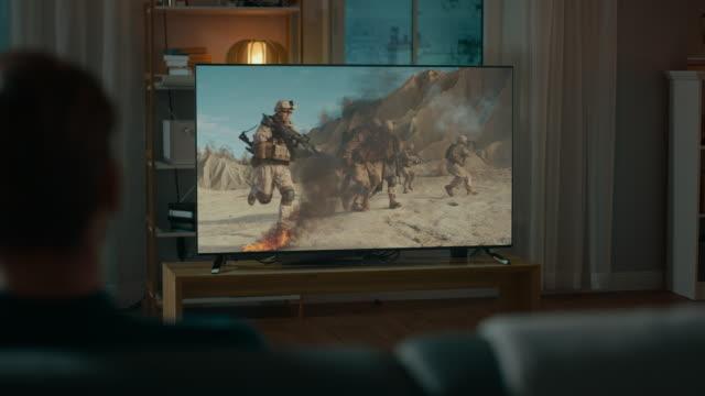 Hombre-relojes-épica-guerra-película-en-la-televisión-sentado-en-un-sofá-en-la-casa-por-la-noche-Acogedor-living-con-luces-cálidas-Sobre-el-tiro-de-hombro-