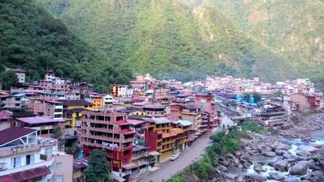 Vista-aérea-de-ciudad-Latina-Gran-río-que-fluye-Montañas-en-el-fondo-