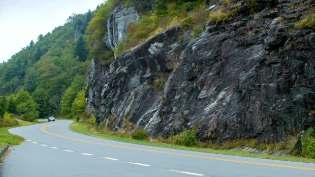Familia-Sedán-por-Blue-Ridge-Parkway-después-de-pared-de-piedra