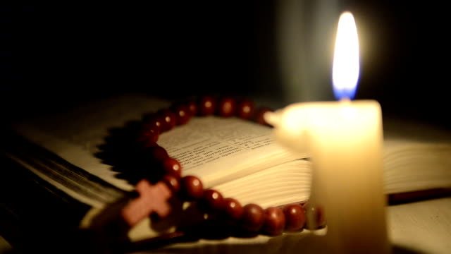 Kerzen-brennen-auf-dem-Hintergrund-der-heilige-Buch-und-einem-cross