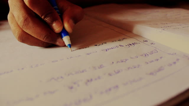 En-primer-plano-de-una-childs-mano-escribir-bengalí