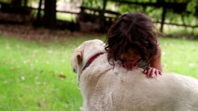 Hispana-niño-jugando-con-el-perro-en-el-parque