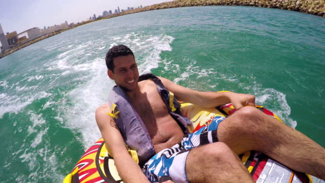 Man-sitting-in-inflatable-ring-towed-by-a-boat-in-the-water-and-recording-himself-with-Go-Pro-camera