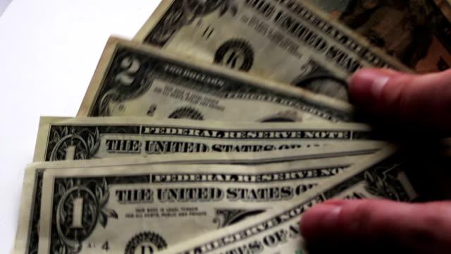 Countslot-mujer-de-pequeños-billetes-de-un-dólar-en-la-tabla-con-una-macro-de-fondo-blanco-de-cerca
