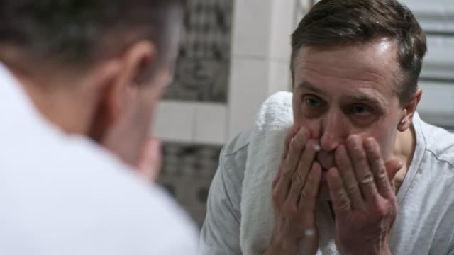 Lavar-y-limpiar-cara-en-el-baño-del-hombre