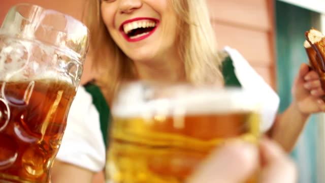 Alkoholvergiftung-ein-junges-Mädchen-trinkt-Bier-auf-dem-Oktoberfest-Festival-sie-ist-sehr-fröhlich-und-lacht-laut-Gekleidet-in-bayrischer-Tracht