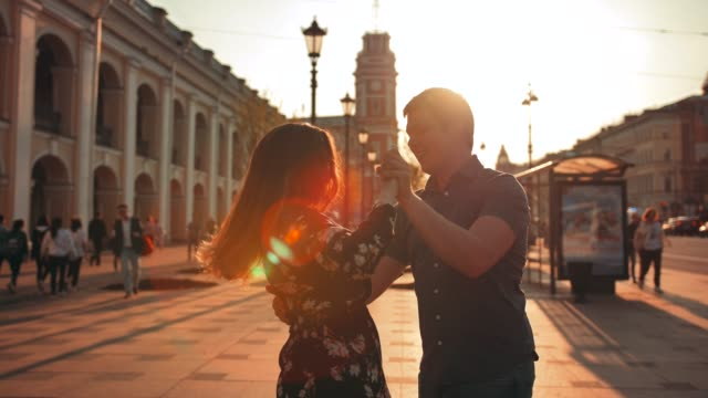 Ein-schönes-Paar-ein-Tanz-mit-Elementen-des-Walzers-tritt-aus-der-Sonne-Sonnenauf--oder-Sonnenuntergang