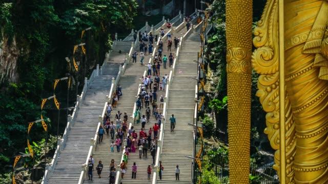 Touristenströme-auf-Stufen-der-Treppe-in-der-Nähe-von-Lord-Murugan-Hindu-Gottheit-Statue-am-Batu-Höhlen-in-Malaysia-Timelapse-4K