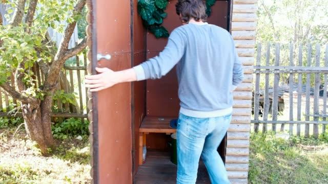 Mann-pisst-in-Außentoilette-mit-einem-Topf-im-Dorf-