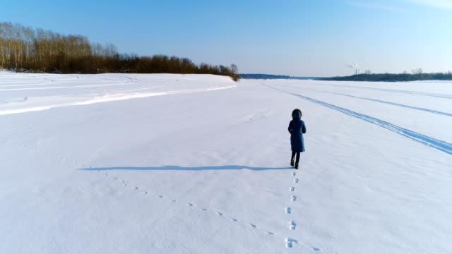 Luftaufnahmen-von-laufenden-Frau-in-Winterlandschaft-eines-gefrorenen-Flusses-mit-einem-Wald-und-einem-Blick-auf-die-Stadt-mit-Fabriken-Hinten-Sie-Ansicht-von-