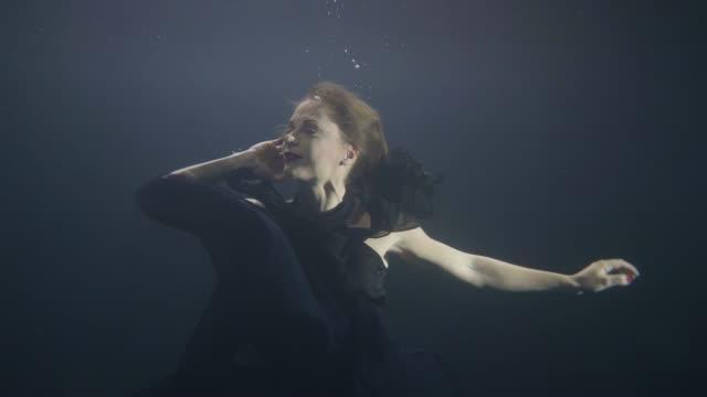 Misteriosa-mujer-en-vestido-negro-nadar-como-sirena-bajo-el-agua-en-la-piscina-oscura