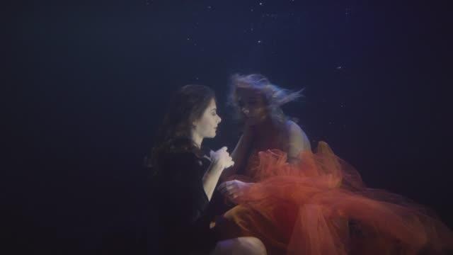 Pareja-a-mujer-lesbiana-en-la-natación-de-Gasa-junto-bajo-el-agua-en-la-piscina-oscura