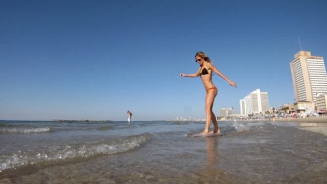 Beautiful-woman-Skim-boarding-at-the-beach-in-slow-motion
