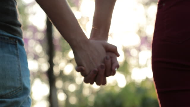 Joining-hands-together-at-the-park-with-sunlight-flare-in-the-background-Concept-of-love-affection-friendship-and-union