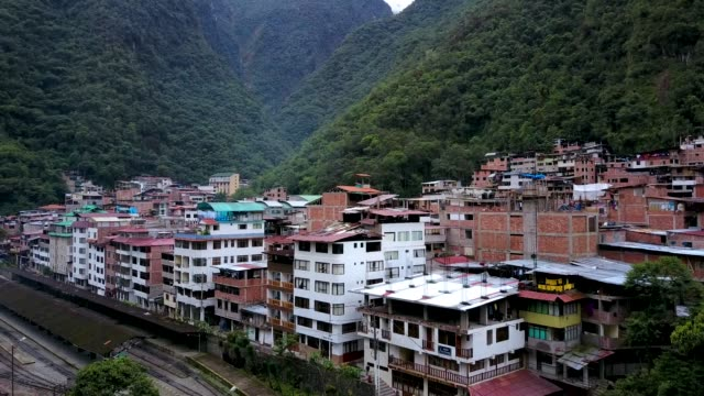 Aerial-view-on-old-Latin-town-Big-river-flowing-Mountains-on-the-background-