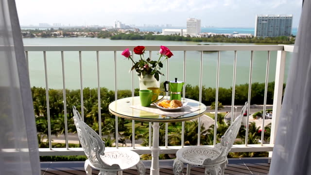 Delicious-breakfast-with-coffee-fresh-croissants-and-slice-of-orange-fruit-on-balcony