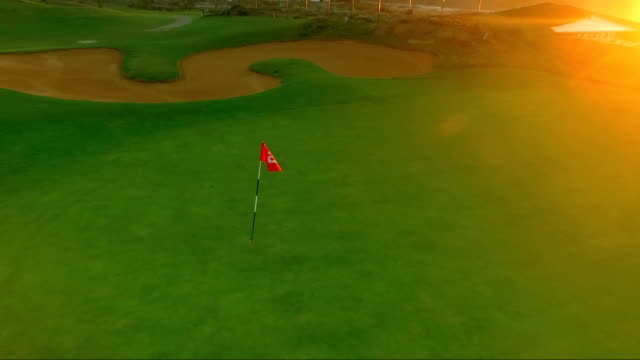 Fly-around-the-golf-pin-on-the-sunset-background
