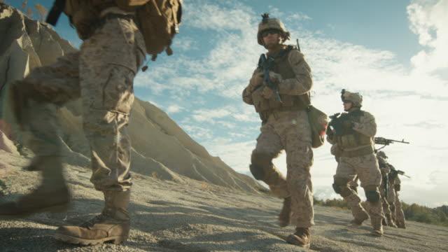 Escuadrón-de-soldados-armados-y-totalmente-equipados-caminando-en-un-solo-archivo-en-el-desierto-Cámara-lenta-