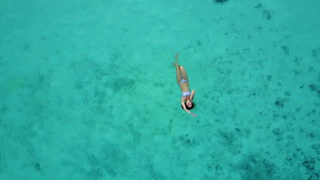 Vista-aérea-de-una-atractiva-mujer-en-un-bikini-flotando-en-el-mar-de-aguas-cristalina-Bonita-hermosa-chica-nadando-en-el-Océano-Índico