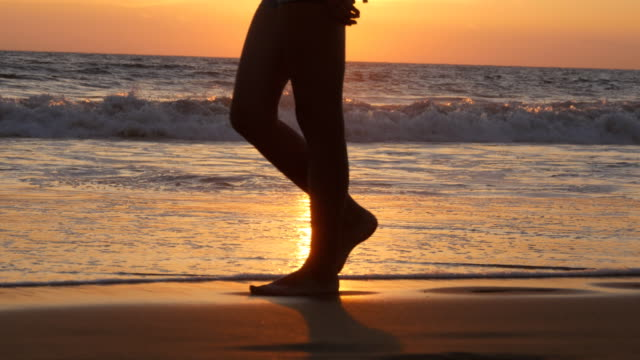 Legs-of-young-woman-going-along-ocean-beach-during-sunrise-Female-feet-walking-barefoot-on-sea-shore-at-sunset-Girl-stepping-in-shallow-water-at-shoreline-Summer-vacation-concept-Close-up