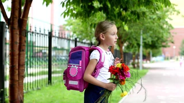 Colegiala-con-mochila-se-despiden-de-ramo-de-flores-y-desaparecer-Chica-de-pie-junto-a-la-escuela-con-bouquet-de-flores-y-backpak-Distorsionarán-fondo-desenfocado-Día-de-verano-al-aire-libre-tiro-de-mano-