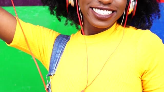 Hübsches-Mädchen-hören-von-Musik-mit-ihrem-Kopfhörer-mit-farbigen-Hintergrund