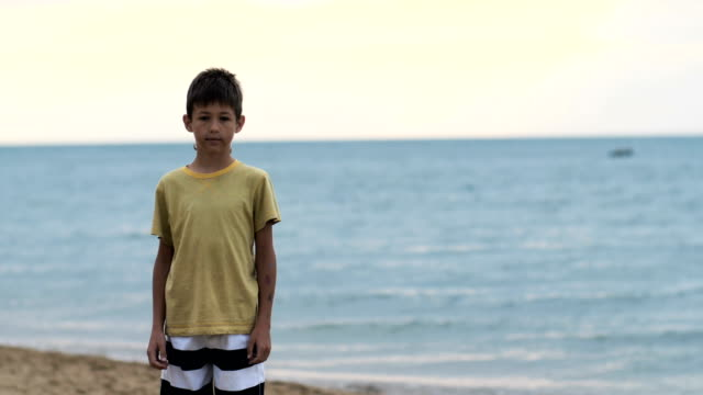 boy-stands-on-the-beach-near-the-sea-and-looks-at-the-camera
