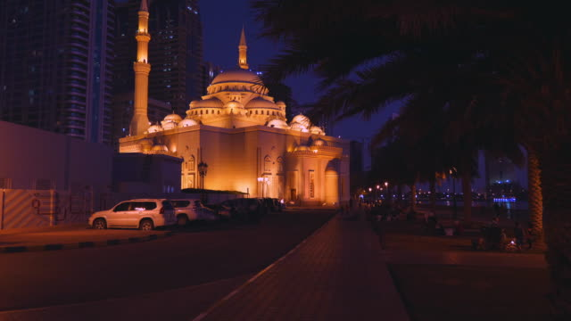 Move-the-camera-to-a-beautifully-lit-mosque-at-night-along-the-alley-