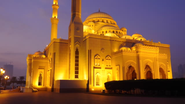Walk-along-the-Arabian-mosque-at-night-A-lone-cyclist-rides-through-the-park-alley-Illuminated-gold-lights-mosque-