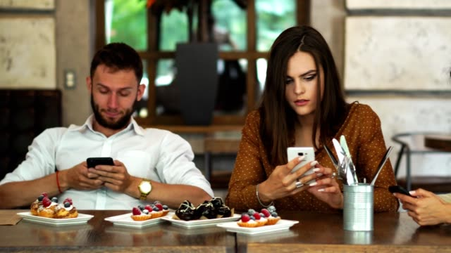 Multi-ethnic-group-of-friends-sitting-in-a-restaurant-and-looking-at-each-of-the-boredom-in-your-phone