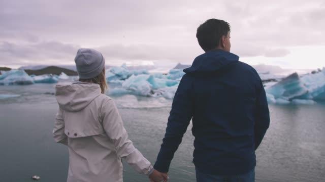 Pareja-joven-en-el-lago-del-glaciar-Jokulsarlon-en-Islandia-tiro-cinemática