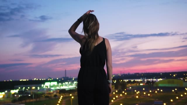 Rear-view-young-woman-enjoying-amazing-view-of-modern-night-city-standing-on-rooftop