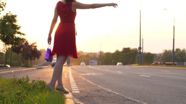 Mujer-en-vestido-rojo-de-autostop-en-la-carretera-hacer-brazo-largo-coche