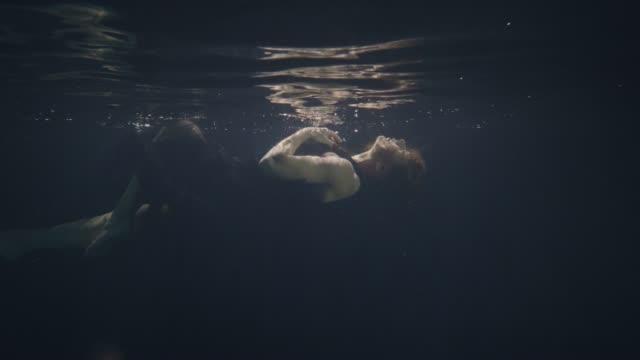 Modelo-en-vestido-negro-para-nadar-bajo-el-agua-sobre-fondo-oscuro
