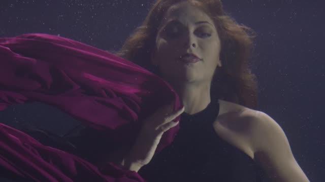Mysterious-woman-in-chiffon-dress-swimming-underwater-pool-on-dark-background-