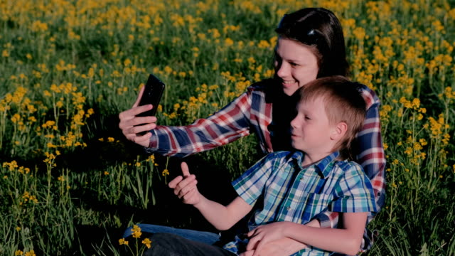 Mom-and-son-make-selfie-on-the-phone-sitting-on-the-grass-among-the-yellow-flowers-