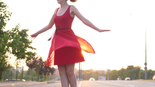 Happy-woman-in-red-dress-dancing-and-turning-around-on-road