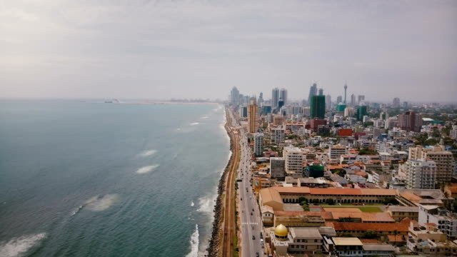 Amazing-aerial-view-of-Colombo-Sri-Lanka-Drone-flying-over-busy-city-street-ocean-waves-and-modern-Asian-architecture