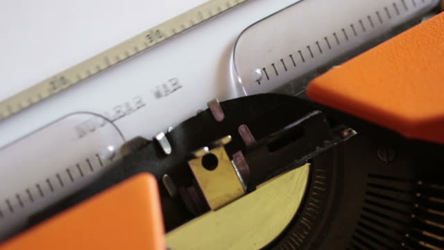 Close-up-footage-of-an-old-typewriter-and-a-person-writing-NUCLEAR-WAR-on-it-